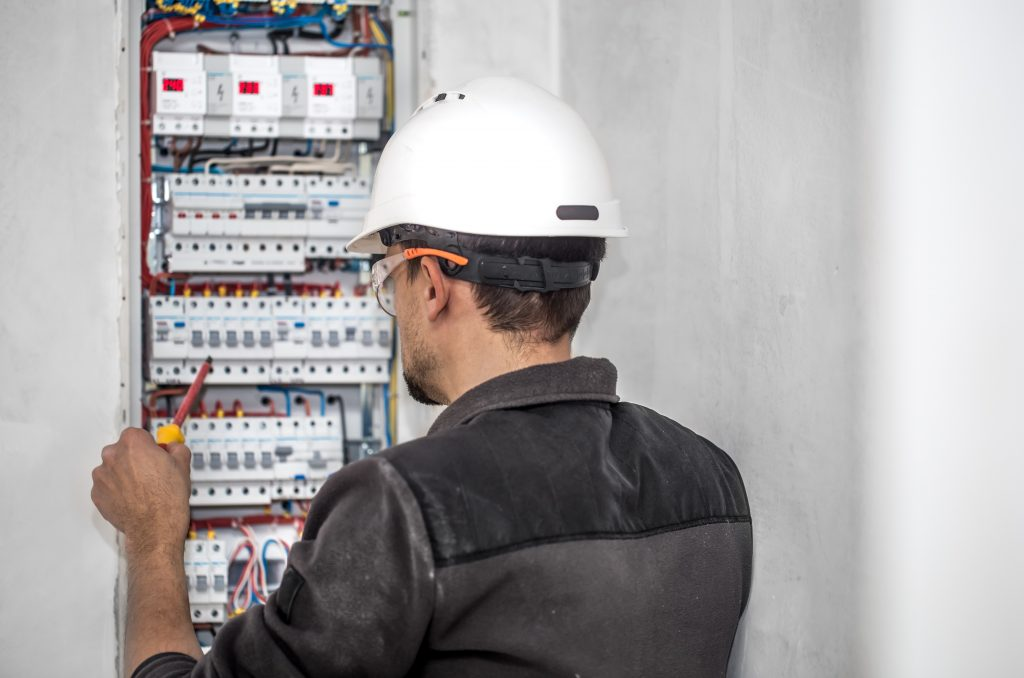 an electrical technician working in a switchboard with fuses. Installation and connection of electrical equipment.